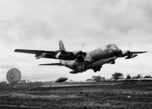 A U.S. Air Force Lockheed C-130A Hercules dropping a pallet with the Low Altitude Parachute Extraction System on Khe Sanh runway, in 1968