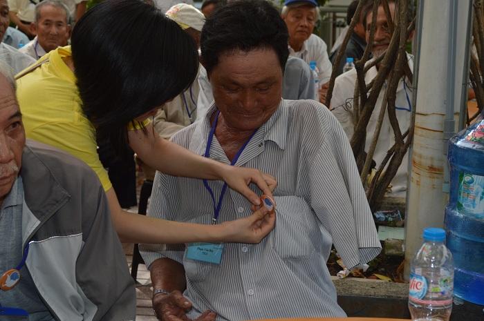 """Một cộng tác viên đeo huy hiệu với dòng chữ  """"Tri ân quý ông thương phế binh 2014 """" cho một thương phế binh"""