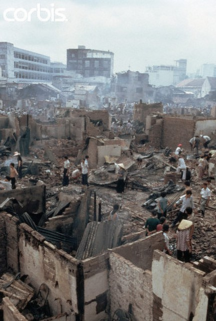 VC pháo kích vào Q1 Saigon tháng 4-1975 (April 1975, Saigon, South Vietnam — War victims walking through rubble after buildings were hit by a Vietcong missile in Saigon, South Vietnam. — Image by © Nik Wheeler/CORBIS)