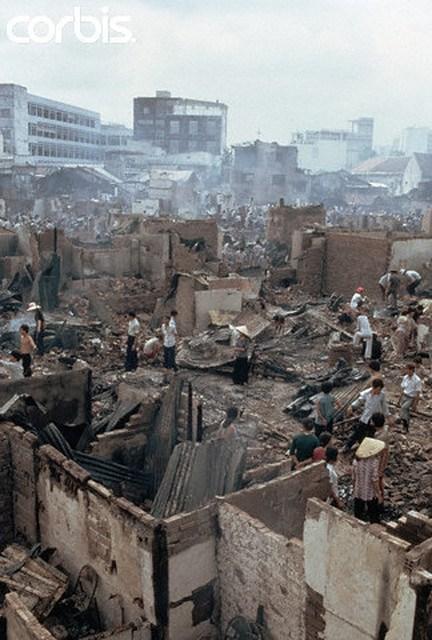 VC pháo kích vào Q1 Saigon tháng 4-1975 (April 1975, Saigon, South Vietnam — War victims walking through rubble after buildings were hit by a Vietcong missile in Saigon, South Vietnam. — Image by © Nik Wheeler/CORBIS)