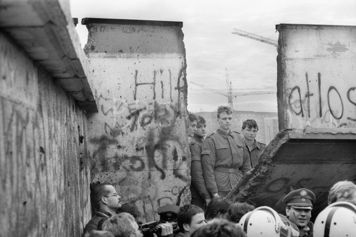 West Berlin East-German soldiers appear behind a piece of the wall torn down by the crowd next to the Brandenburg Gate on November 11, 1989 .