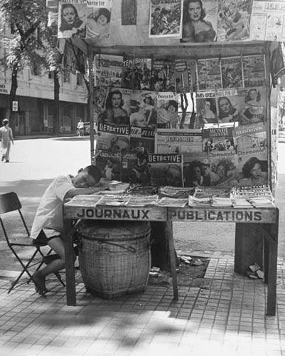 Một trẻ bán báo đang nghĩ mệt bên cạnh sạp báo và tạp chí.