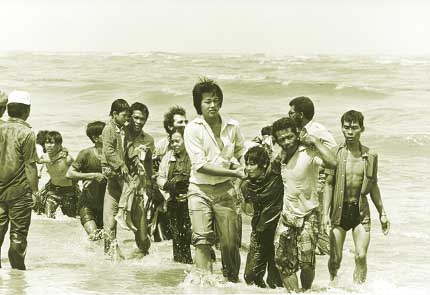 MALAYSIA - JANUARY 1:  A picture taken in the late 1970s shows a group refugees (162 persons) arrived on a small boat which sank a few meters from the shore in Malaysia. The flight of Vietnamese refugees began after the fall of Saigon in 1975. In spite of the dangers of unfriendly waters and piracy, tens of thousands took the South China Sea, and by 1978 the exodus had grown to dramatic proportions.  (Photo credit should read K. GAUGLER/AFP/Getty Images)