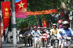 xe gắn máy chạy dưới cờ và băng rôn chào mừng Quốc Khánh lần 65 tại Hà Nội hôm 31/8/2010. AFP photo/Hoang Dinh nam