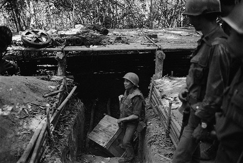 Ho Chi Minh Trail, Laos --- 02/14/71- Ho Chi Minh Trail, Laos: An ARVN soldier hauls out some of the supplies from a bunker discovered on the Ho Chi Minh Trail. North Vietnamese used the bunkers as storage depots and protective cover. Caches of Gasoline, weapons and uniforms have been uncovered. UPI radiophoto by Bob Sullivan. --- Image by © Bettmann/CORBIS