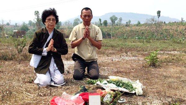 Bà quả phụ Nguyễn Văn Ðương và con trai Nguyễn Viết Xa khấn vái vong linh của chồng và cha trên đỉnh đồi 31, Hạ Lào. (Hình: Việt Hùng/Người Việt)