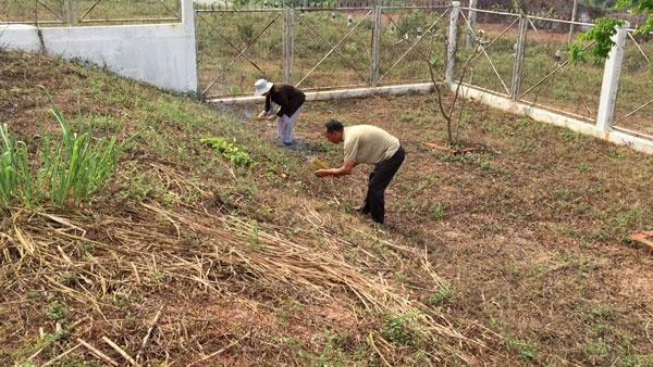 Hai mẹ con bà Mai thắp nhang khắp khu đồi 31. (Hình: Việt Hùng/Người Việt)